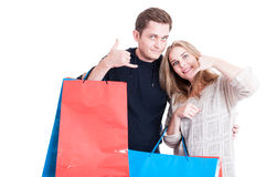 Couple holding shopping bags making calling gesture Stock Photography