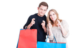 Couple holding shopping bags making fingers crossed gesture Royalty Free Stock Image