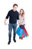 Couple holding shopping bags showing empty pockets. Full body of couple holding shopping bags showing empty pockets like spending too much isolated on white Royalty Free Stock Photos