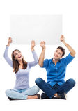 Couple holding sign above their heads Royalty Free Stock Photo
