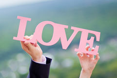 Couple holding a sign love Royalty Free Stock Photos