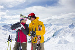 Couple holding skis standing on mountain top together Royalty Free Stock Photos