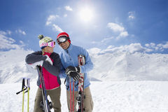 Couple holding skis standing on mountain top together Stock Photo