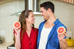 Couple holding slices of blood orange Stock Photo
