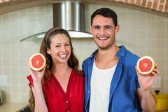 Couple holding slices of blood orange Stock Images