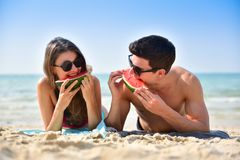 Couple holding slices of watermelon stock photo