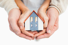 Couple holding small model house in hands. On white background Stock Images