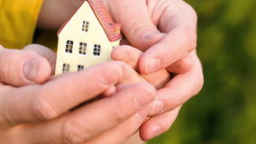 Couple holding a small toy house in hands stock video