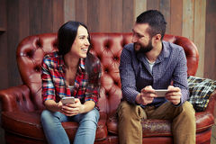 Couple holding smartphones and looking at each other Stock Photography