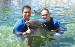 Couple Holding a Smiling Dolphin !. Man and Woman holding a smiling dolphin Royalty Free Stock Photo