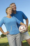 Couple Holding Soccer ball Looking away Stock Image