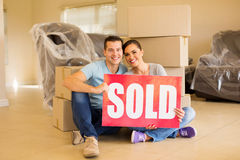 Couple holding sold sign. Beautiful couple holding sold sign surrounded by cardboard boxes stock photo