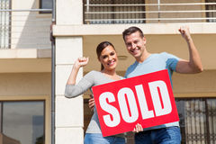 Couple holding sold sign. Cheerful young couple holding sold sign in front of their old house royalty free stock images