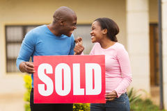 Couple holding sold sign. Excited black couple holding sold sign outside their house stock image