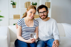 Couple holding sonogram. A portrait of a couple holding a sonogram Royalty Free Stock Images