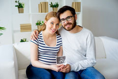 Couple holding sonogram. A portrait of a couple holding a sonogram Royalty Free Stock Photos