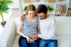 Couple holding sonogram. A portrait of a couple holding a sonogram Stock Photo