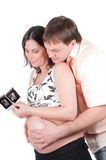 Couple holding a sonogram of their child Royalty Free Stock Images