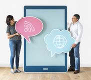 Diverse people holding speech bubbles and tabletCouple holding speech bubbles and tablet stock photography
