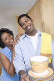 Couple Holding Stack Of Washed Plates And Bowl Stock Images
