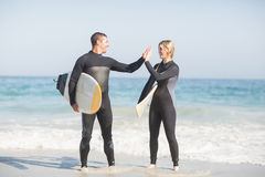 Couple holding a surfboard and giving a high five to each other Royalty Free Stock Photos