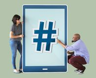 Couple holding tablet icons with hashtag Royalty Free Stock Images