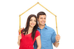 Couple holding tape measure over their heads Stock Images