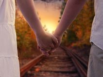 Couple Holding in Train Rails during Golden Hour Stock Images