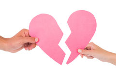 Couple holding two halves of broken heart Stock Photo
