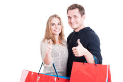 Couple holding up shopping bags making thumb up gesture royalty free stock photo
