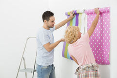 Couple holding up wallpaper samples in new house Stock Photo
