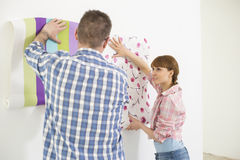 Couple holding up wallpaper samples in new house Stock Images
