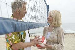 Couple Holding Volley Ball At Beach Stock Images