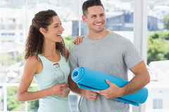 Couple holding water bottle and exercise mat Stock Photography
