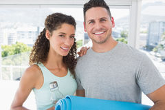 Couple holding water bottle and exercise mat at gym Stock Image