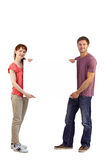 Couple holding a white sign Royalty Free Stock Image