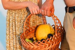 Couple holding a wicker basket with fruit, man and woman having a picnic on the white sand beach or in the desert or in the sand d. Couple holding a wicker Royalty Free Stock Images