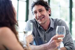 Couple holding wine glass and interacting. At dining table in the restaurant Stock Images