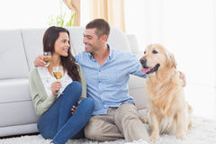 Couple holding wine glasses while sitting with dog Stock Images