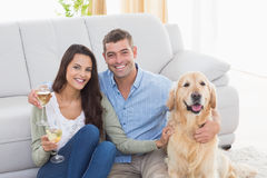 Couple holding wine glasses while sitting with dog Stock Photography