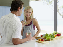 Couple Holding Wineglasses At Kitchen Counter royalty free stock image