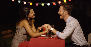 Couple holds hands across table and smiles Royalty Free Stock Image