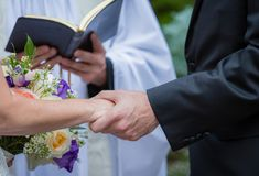 Couple holds hands while saying vows during wedding. In summer stock images