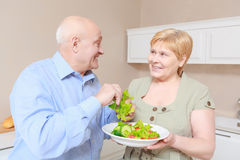 Couple holds a plate with salad Royalty Free Stock Photos