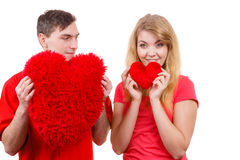 Couple holds red heart shaped pillows love symbol. Couple. Boyfriend and his girlfriend holding red heart shaped pillows love symbol. Romantic women and men royalty free stock images