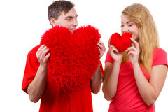 Couple holds red heart shaped pillows love symbol. Couple. Boyfriend and his girlfriend holding red heart shaped pillows love symbol. Romantic women and men stock photo