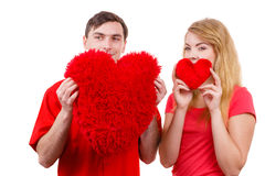 Couple holds red heart shaped pillows love symbol. Couple. Boyfriend and his girlfriend holding red heart shaped pillows love symbol. Romantic women and men royalty free stock photos