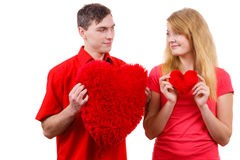 Couple holds red heart shaped pillows love symbol. Couple. Boyfriend and his girlfriend holding red heart shaped pillows love symbol. Romantic women and men royalty free stock photo