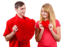 Couple holds red heart shaped pillows love symbol Royalty Free Stock Image