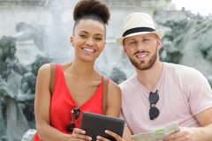Couple at holiday landmark holding tablet and map. Couple royalty free stock image